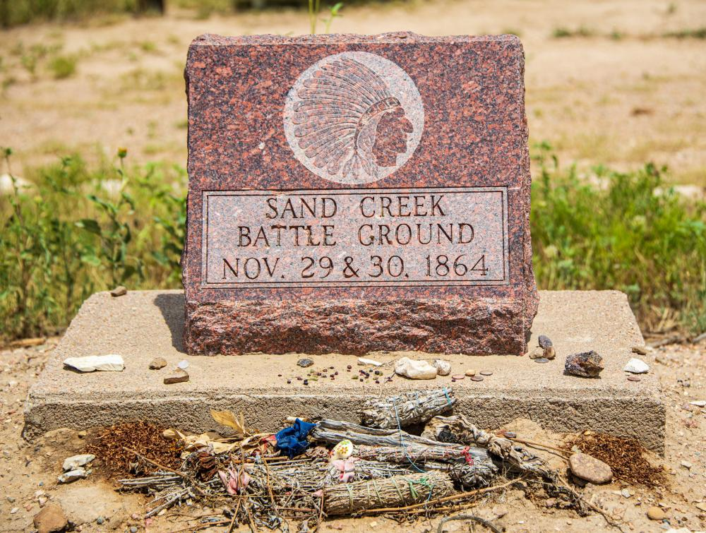 "Monument reading ""Sand Creek Battle Ground, Nov. 29 & 30, 1864"" with rocks and other items left in front of it, Sand Creek Massacre National Historic Site, Colorado"