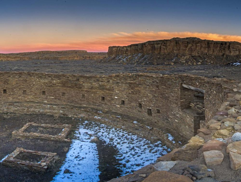 A view of the Chaco Canyon ruins with the sunset on the background.