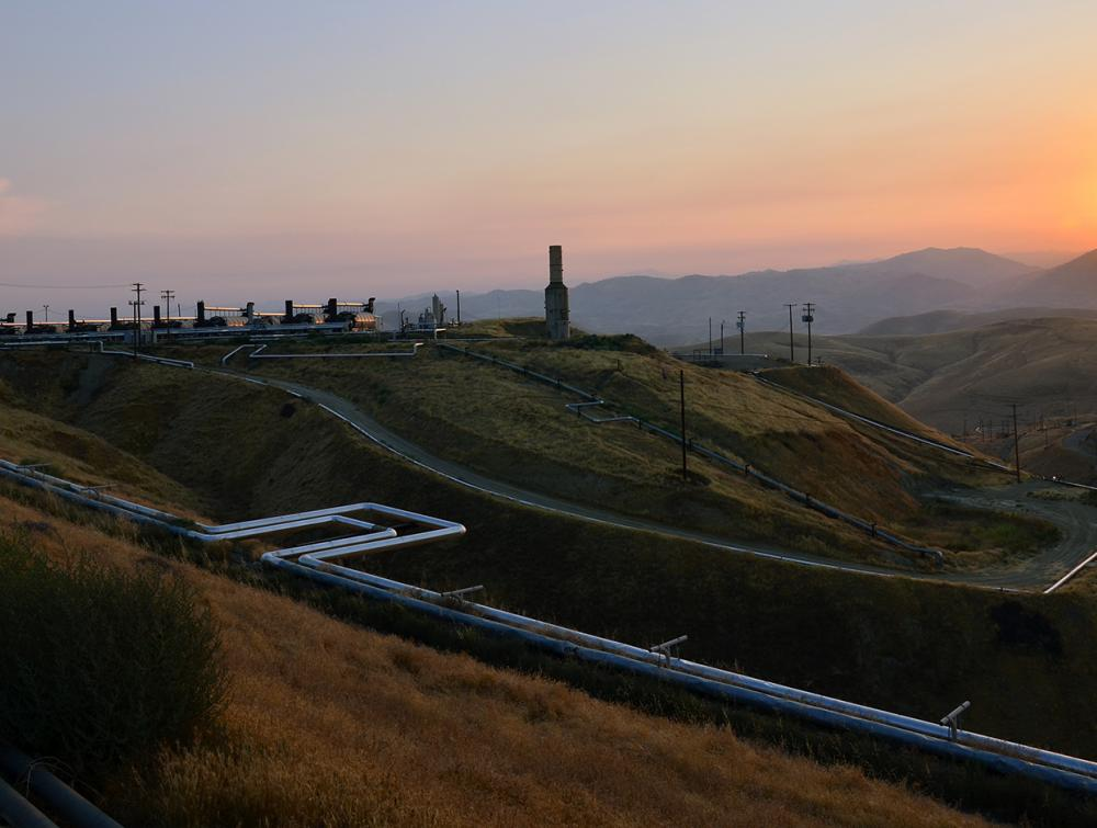 Oil and gas facility on a hill as the sun sets.