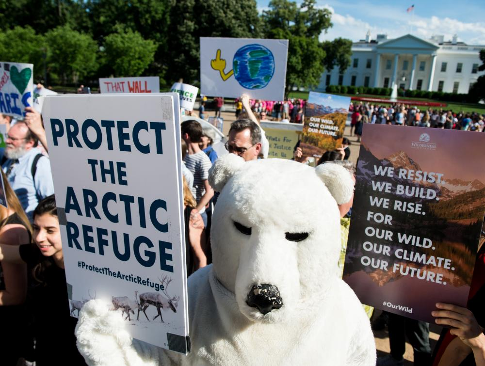 Environmental activists protest in front of the White House after President Donald Trump announced he is withdrawing the United States from the Paris climate accord on Thursday, June 1, 2017.