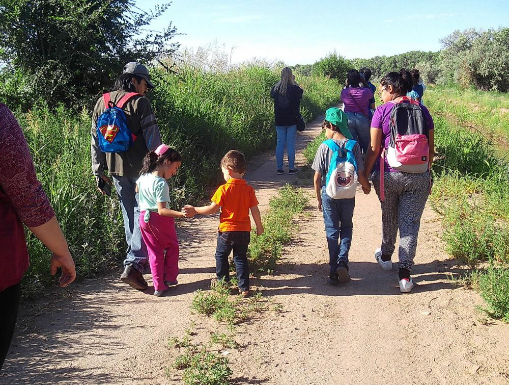 Two small children hold hands with other people while walking down a trail away from the camera