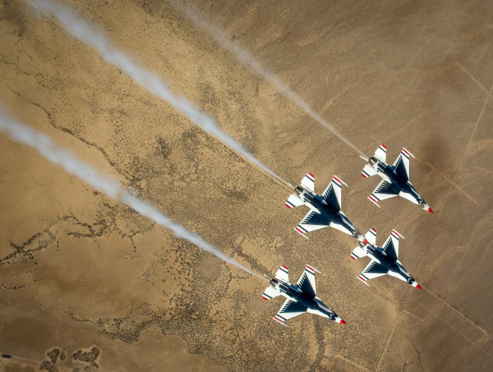 Overhead view of four military-style jets flying above a desert landscape