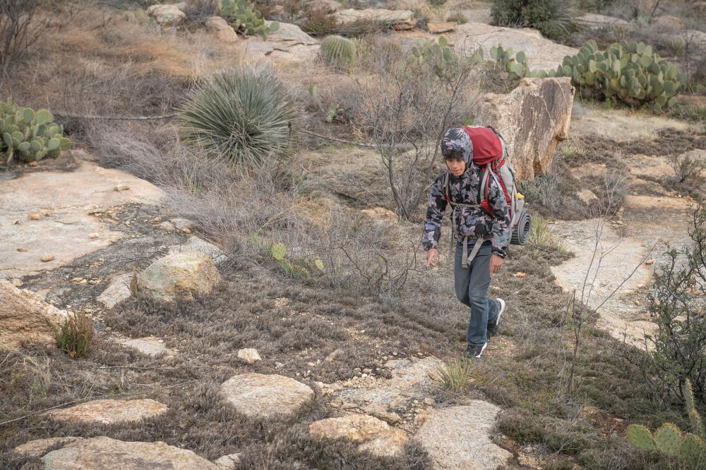 Young hiker walking over rocks and past desert plants in Saguaro National Park, Arizona