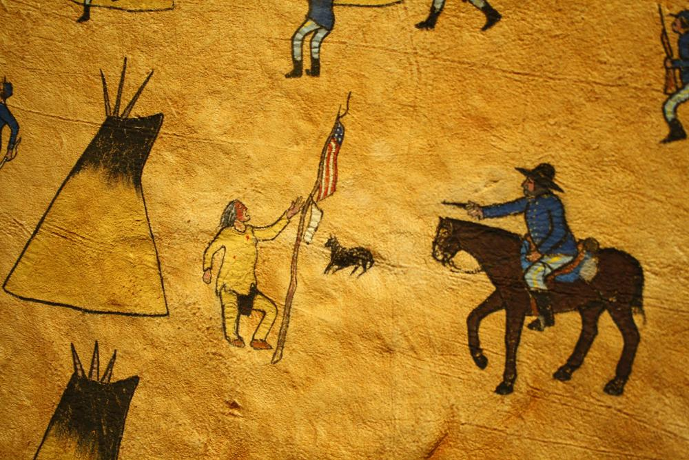 painted image of cavalryman on horseback, pointing gun at a Native American