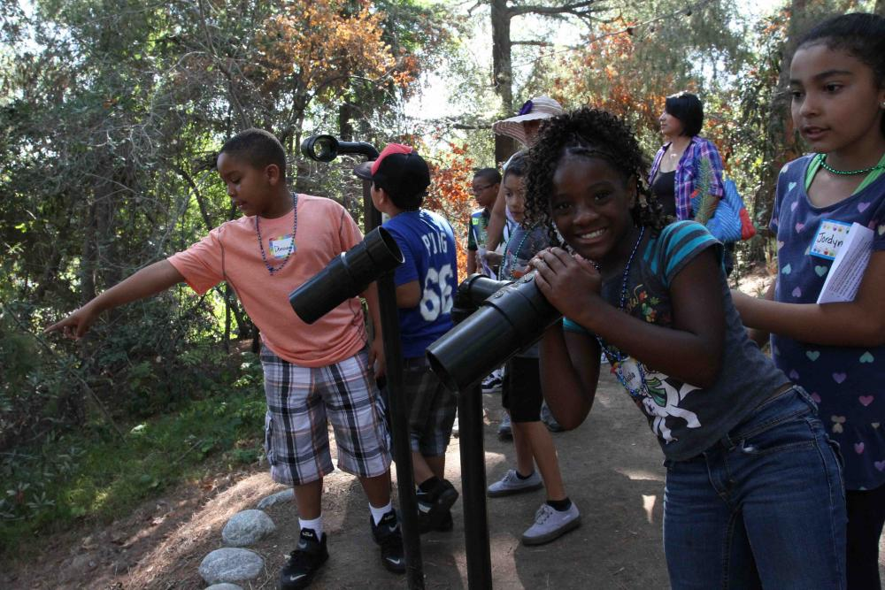 "Girl looks through mounted telescope in a group of kids at an ""Every Kid in a Park"" event in Los Angeles County, California, in 2015"