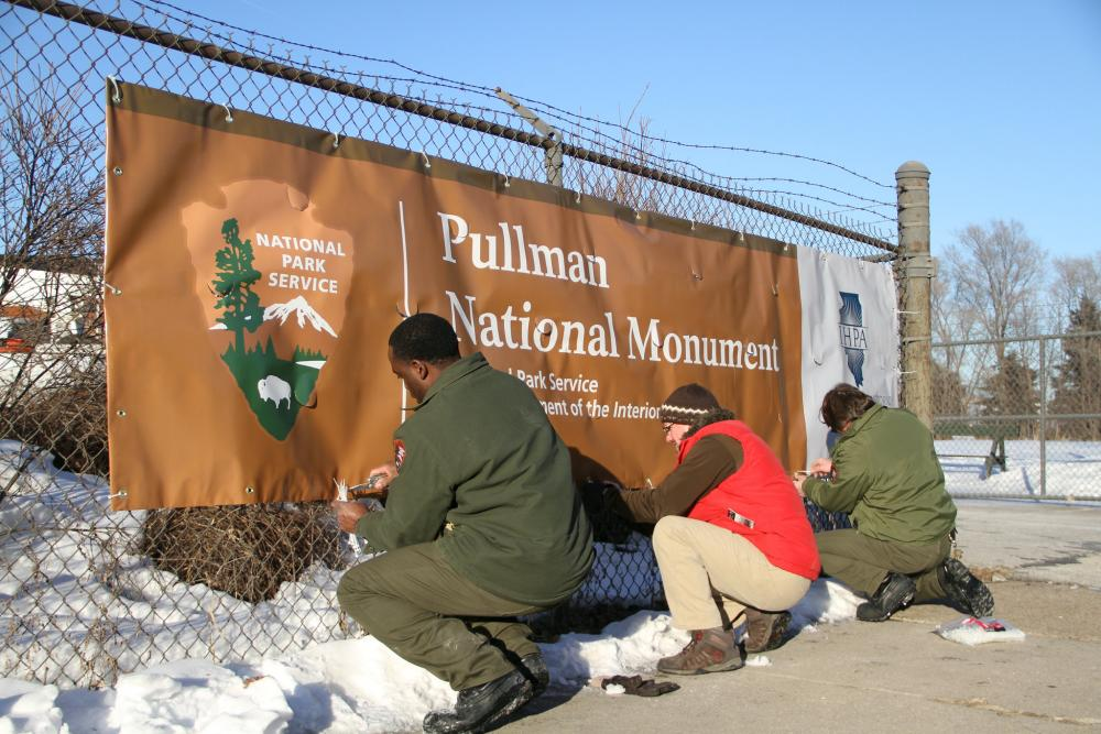 "Three people kneel while securing a banner that reads ""Pullman National Monument"" against a chain-link fence"