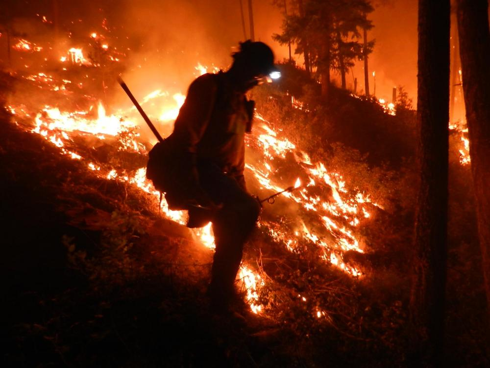 A firefighter in front of a wildfire in Lolo National Forest, Montana