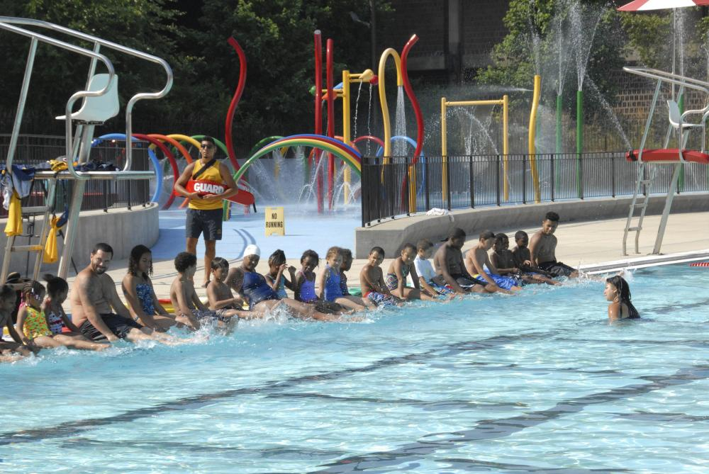 A row of children sit on the edge of a swimming pool at Roberto Clemente State Park in the Bronx, New York