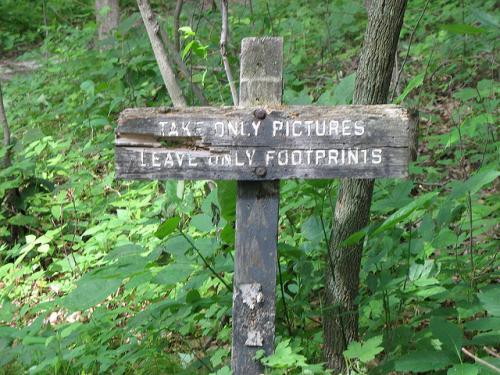 "Sign in park that reads ""Take only pictures. Leave only footprints"""